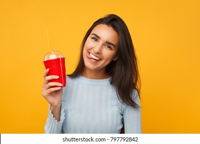 Brunette cheerful girl holding a soda cup on yellow background. Thirsty happy young woman with a glass of beverage
