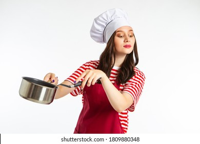 The brunette is a chef. A girl in a chef costume with a laddle in her hands. Culinary concept. Cooking. Interesting recipes. Cooking blog.