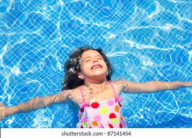brunette children girl swimming in blue tiles pool floating closed eyes
