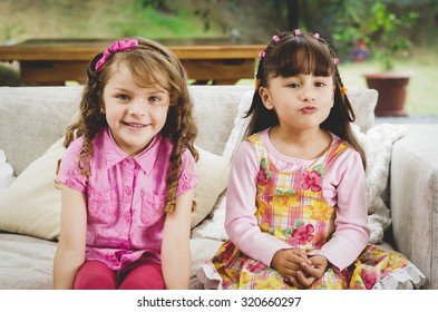 Brunette children sisters sitting happily on white livingroom sofa posing for camera with typical pink girl clothes.