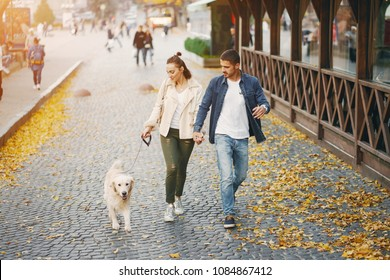 brunette couple walking their golden retriever dog in the city on a sunny autumn day