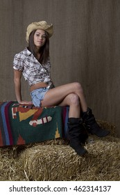 brunette cowgirl sitting on a blanket set on bales of straw