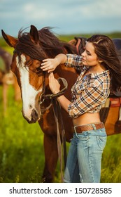 brunette cowgirl woman standing with horse outdoors portrait