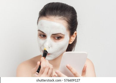 brunette with cream on her face and brush for makeup..