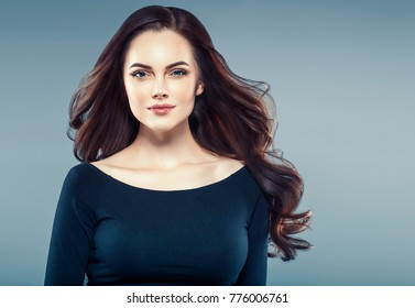 Brunette curly hair. Beautiful woman with long beauty healthy hair portrait