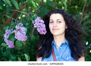 Brunette with curly hair near a lilac bush