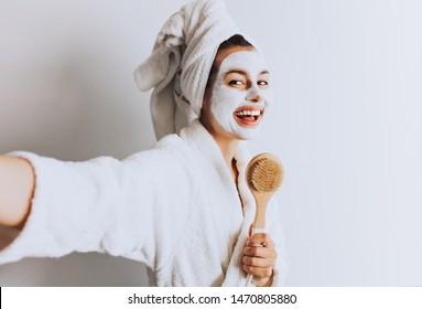 Brunette süße junge Frau singen mit erfrischender Wellness-Maske und machen sich selbst im hellen Raum zu Hause. Morgenwache/Körperpflege-Konzept