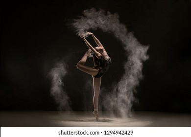 Brunette dancing gracefully in white dust cloud