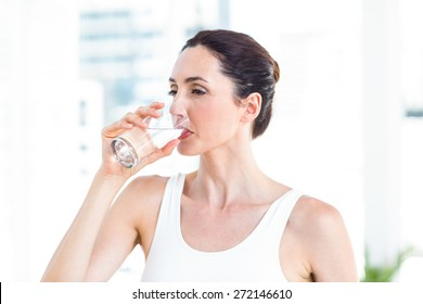 Brunette drinking water in the living room