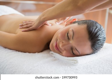 Brunette enjoying a peaceful massage with eyes closed at the health spa
