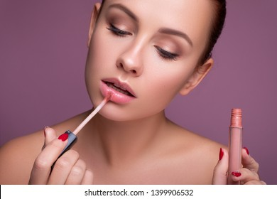 Brunette european woman apply lipstick on her lips on pink neutral background. Flawless clean fresh skin. Beauty process concept