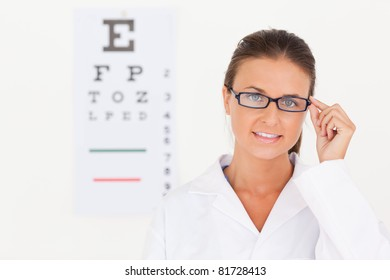 Brunette eye specialist wearing glasses looking into the camera in her surgery