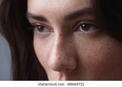 brunette face on the light grey background