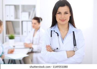 Brunette female doctor on the background of colleagues talking to each other in hospital. Medicine and health care concept