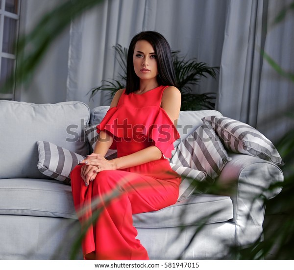 A brunette female dressed in a red evening dress sits on a coach in a room with green plants and grey interior.