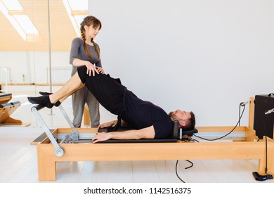 Brunette female instructor with cute braids hairstyle consulting hansdome beard man workout pilates on reformer practice in pilates studio, working out indoor, correcting beginners, full length.