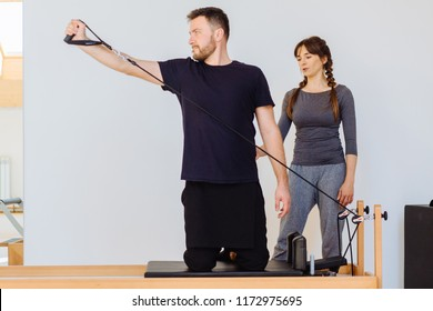 Brunette female instructor with cute two braids hairstyle consulting hansdome beard man workout pilates on reformer practice in pilates studio, working out indoor, correcting beginners, full length.