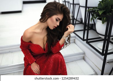 Brunette female with long volume hair lying on shoulder, sitting on white steps.Wearing red evening dress with open shoulders and decollete.Stylish makeup for the party.Tender soft skin, head lean on