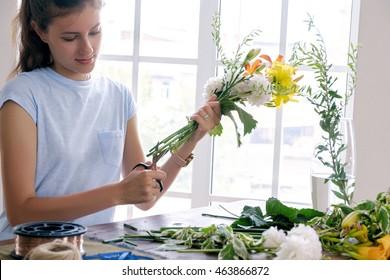 brunette florist cutting flowers with scissors in workshop