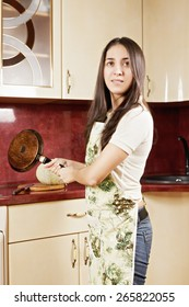 Brunette with frying pan at the kitchen