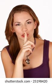 Brunette gesturing for silence with finger on lips