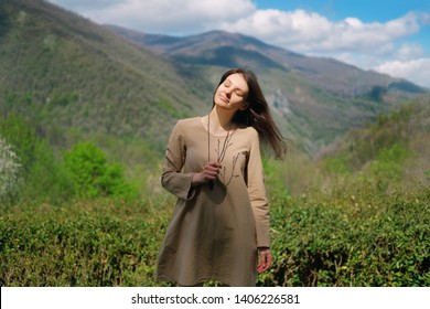 Brunette girl in beige linen dress standing on background of green caucasus mountains in Sochi, Russia. Freedom ecology lifestyle concept