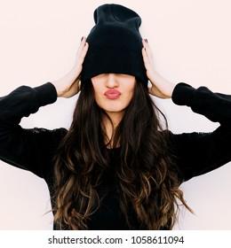 Brunette Girl in black beanie cap. Fashion Tomboy style