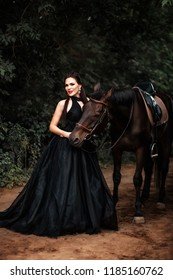 A brunette girl in a black dress next to a horse in the woods.