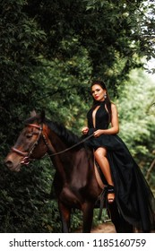A brunette girl in a black dress on a horse in the woods.