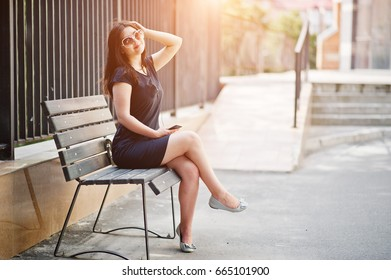 Brunette girl at black dress, sunglasses sitting on bench, listening music from headphones phone, and posing at street of city.