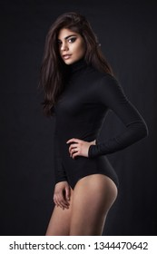 Brunette girl in a black leather jacket . Beautiful model on a dark background. Studio photosession