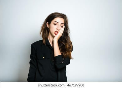 brunette girl is bored, dressed in black, isolated on white background