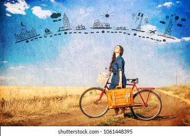 Brunette girl  with bycicle and suitcase on country side road and abstract travel map in air