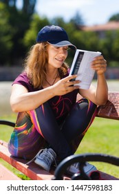 brunette girl with a cap, reading a book sitting on a bench