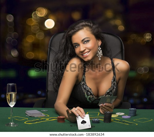 brunette girl in the casino playing poker, shows a playing card