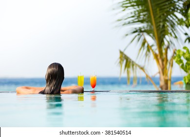 Brunette girl with cocktails relaxing in swimming pool, ocean on background