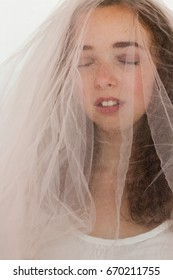 brunette girl covered in tulle with eyes closed