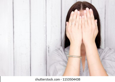 brunette girl covers her face with her hands, lifestyle concept studio photo on a gray background. concept of social phobia