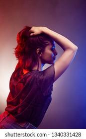 brunette girl dancing. red and blue disco backlit