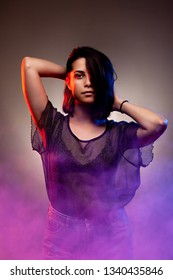 brunette girl dancing. red and blue disco backlit and purple smoke