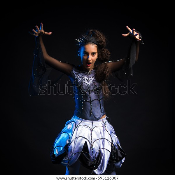 brunette girl in a dancing suit the queen spider posing on a black background in the studio