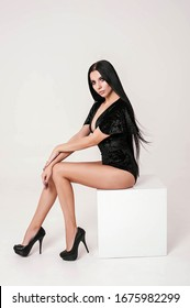 A brunette girl dressed in a black bodysuit with corduroy ruffles shod in black heels on a white background on a cyclorama sits on a white cube posing