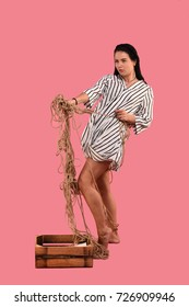 brunette girl dressed in stripes dress with a rope
