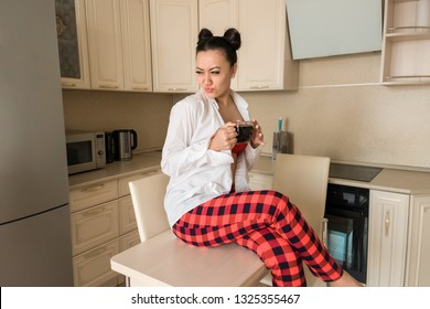 fefb4688f9 Brunette girl drinking black coffee at home in the kitchen. The girl sitting  at the
