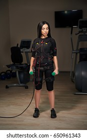 Brunette girl in Electrical Muscular Stimulation suit standing with dumbbells. Glowing effect. Gothic style. EMS.