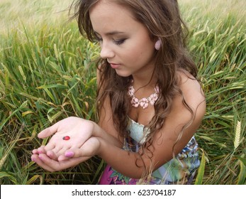 brunette girl in a field with ladybug on her hands