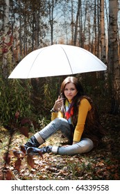 Brunette girl in the forest under light umbrella