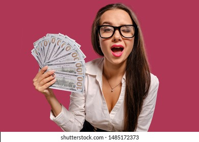 Brunette girl in glasses, wearing in a black short skirt and white blouse is posing holding a fan of hundred dollar bills against a pink background.