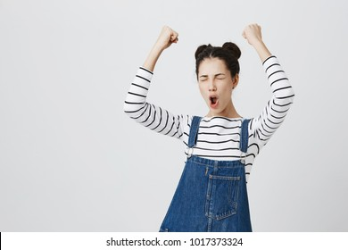 Brunette girl with hairbuns in striped top excited and glad to achieve victory, clenches fists, screams in excitement with closed eyes, happy to pass all exams at university, successful person.