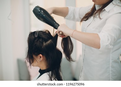 Brunette girl at the hairdresser doing styling